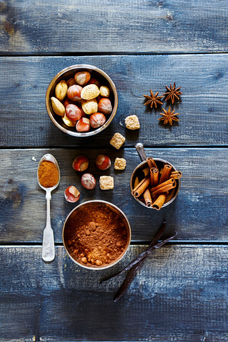 Baking concept background with aromatic spices and nuts over dark wood