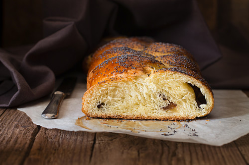 Sweet bread with poppyseeds, sliced on a piece of baking paper