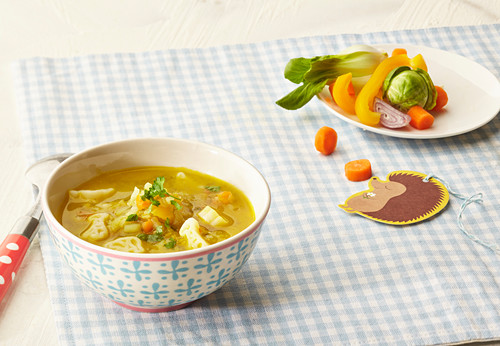 Vegetable soup with noodles in a little bowl with ingredients