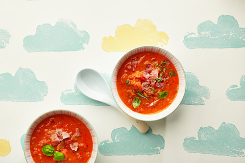 Two bowls of tomato soup with bacon