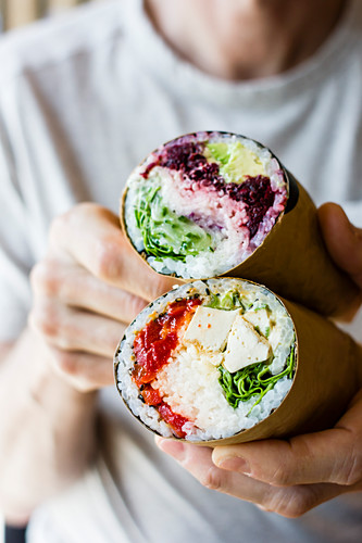 Sushi burritos being held in a persons hands