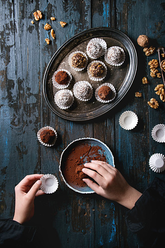 Child hands make homemade dark chocolate truffles with cocoa powder, coconut, walnuts, put on vintage tray