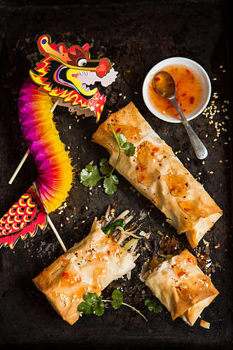 Two homemade vegetable spring rolls one torn open sprinkled with chilli flakes and sesame seeds and fresh coriander with sweet chilli sauce and a celebration paper dragon