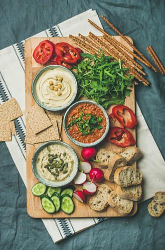 Various Vegetarian dips: Hummus, babaganush and muhammara with crackers, bread and fresh vegetables on wooden board