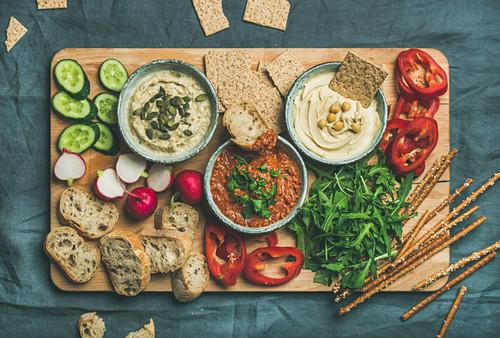 Various Vegetarian dips: hummus, babaganush and muhammara with crackers, bread, fresh vegetables on wooden board