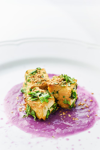 Natural tofu sauteed in a pan finished with aromatic grass on cabbage and ginger cream thicken with rice flour