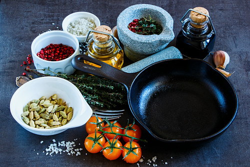 Dark vintage board with olive oil, balsamic vinegar, mortar and pestle with various colorful spices and vegetables