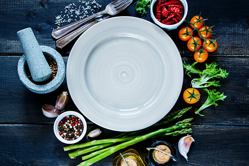 Various colorful spices and vegetables around empty plate on rustic wooden background