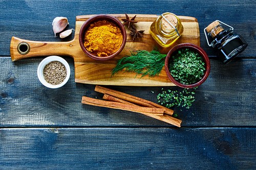Tasty cooking concept background with wooden cutting board and spices selection on vintage kitchen table