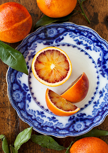 A blue and white plate with pieces of blood orange, with whole blood oranges and leaves in the background