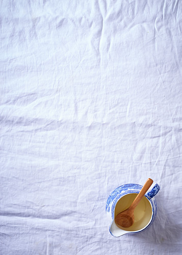 Oil in a porcelain jug with a wooden spoon
