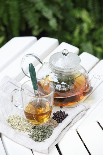 Herbal tea against nausea in a glass teapot and a glass cup