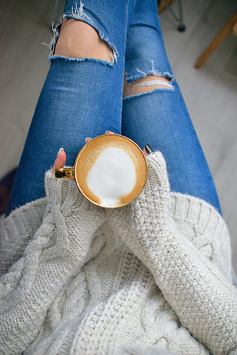 A woman holding a cup of coffee in her hands