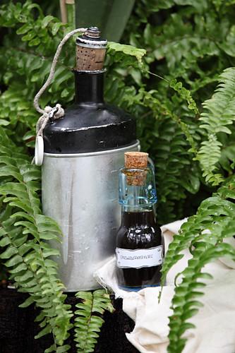Spitzwegerichtinktur in kleinem Fläschen neben alter Feldflasche