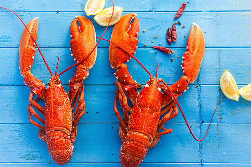 Two cooked lobsters with lemon wedges