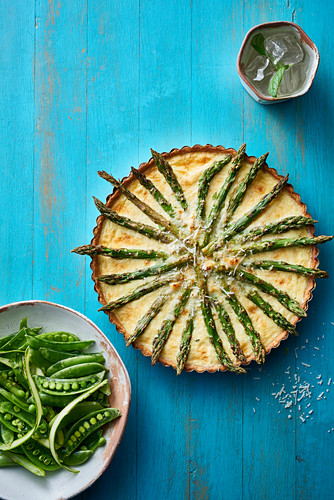 Asparagus tart with grated cheese springled across the top and served with fresh garden peas