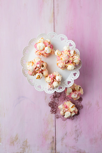 Marshmallow popcorn balls on a pink surface (seen from above)