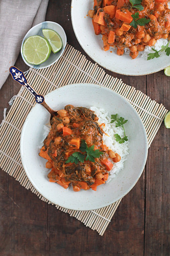 Sweet potato and chickpea curry with spinach and limes on a wooden mat