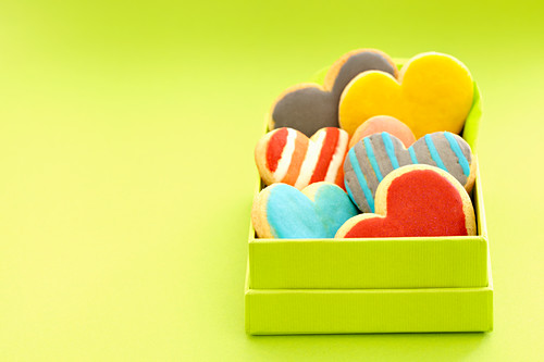Heart cookies with colorful icing in a box in front of a green background