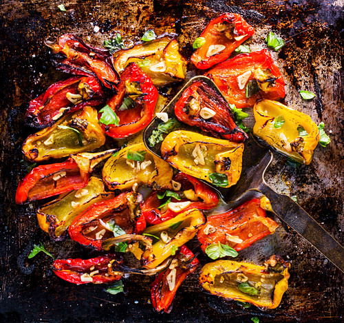 Roasted peppers with garlic and basil on an oven tray (top view)