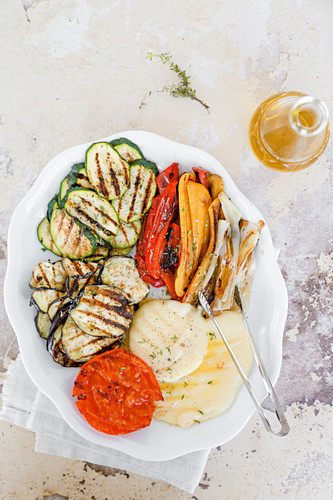 Dish with grilled vegetables, courgettes, aubergines, peppers, tomatoes, spring onions, and scamorza