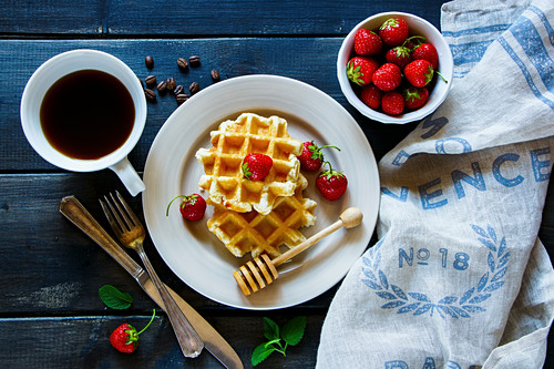 Breakfast belgian waffles stacked on a plate, served with coffee, fresh strawberries and mint at textile napkin over old wooden table