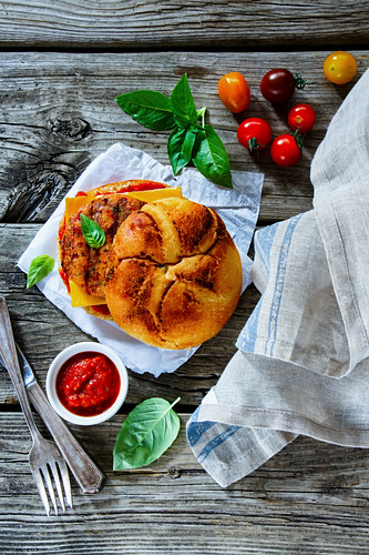Tasty fish and crab burger with spicy tomato sauce and basil over grey rustic wooden background