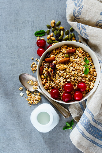 Tasty granola, nuts and berries, muesli with fresh cherries, mint and milk or yogurt bottle