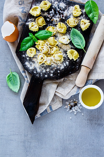 Top view of freshly made raw Italian pasta tortellini, olive oil, flour and basil leaves on light grey vintage background