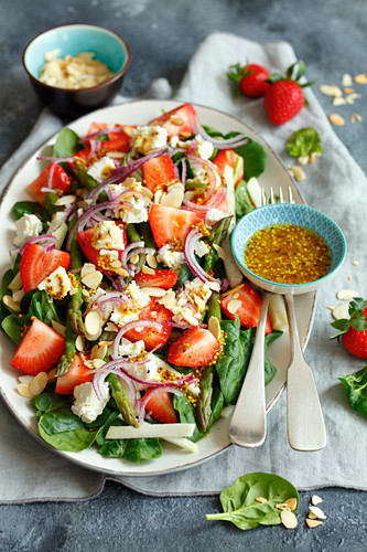 Spinach salad with strawberries, green asparagus, feta cheese and almonds