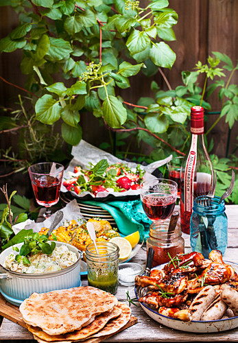 Grill buffet with meat, sausage, flatbread, salad and wine