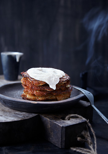 A stack of potato fritters on a plate against a dark background