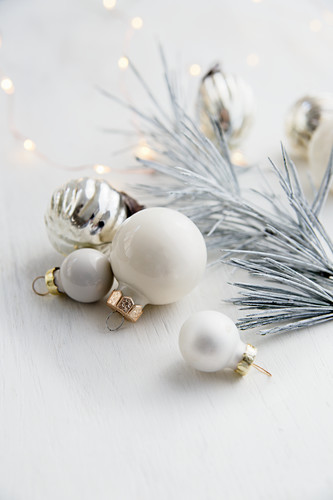 Christmas bauble decorations and white fir tree with Christmas lights
