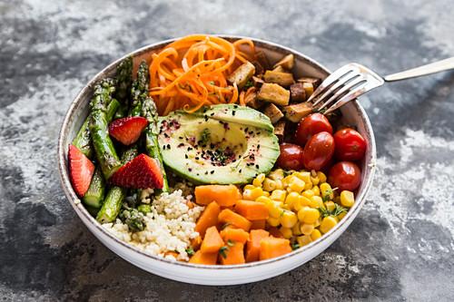 A Buddha bowl with bulgur, green asparagus, strawberries, carrots, tofu, tomatoes, sweetcorn, sweet potatoes and avocado