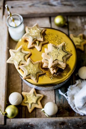 Festive star sugar cookies with golden royal icing and sprinkles on golden and white cookie tin for a gift