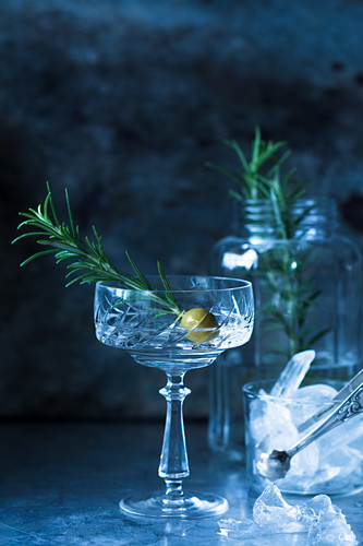A drink garnished with an olive and a sprig of rosemary