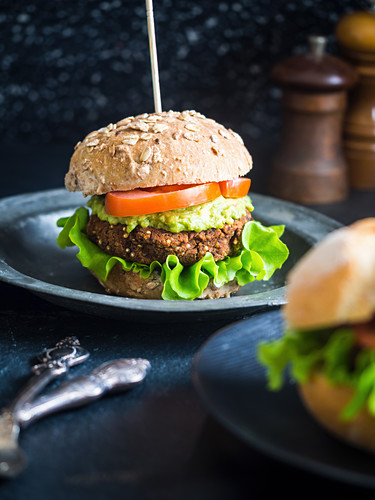 Healthy vegan quinoa and red beans burger sandwich with guacamole, fresh lettuce and tomatoes, served on a whole grain bun