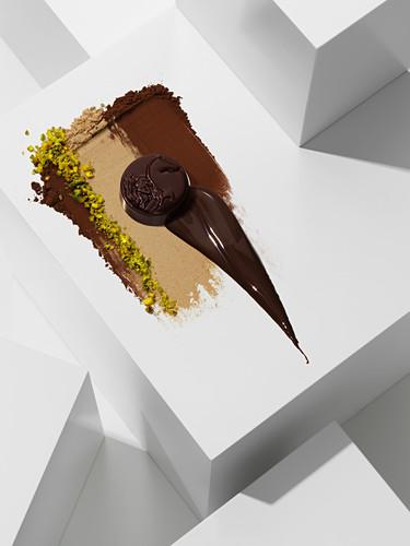 Dark chocolate praline on various chocolate textures with pistachios