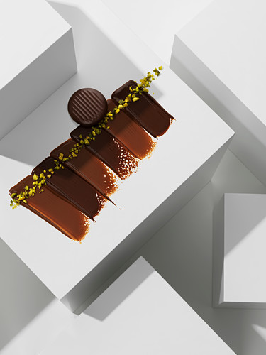 A chocolate praline on various chocolate textures with pistachios