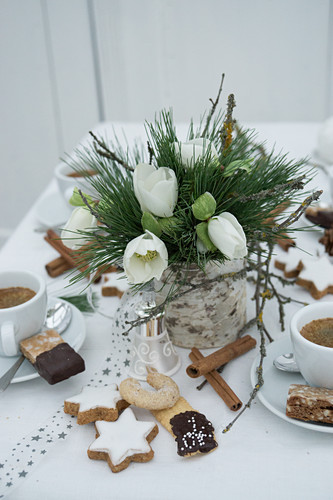 Table set with Christmas biscuits and vase of hellebores for afternoon coffee