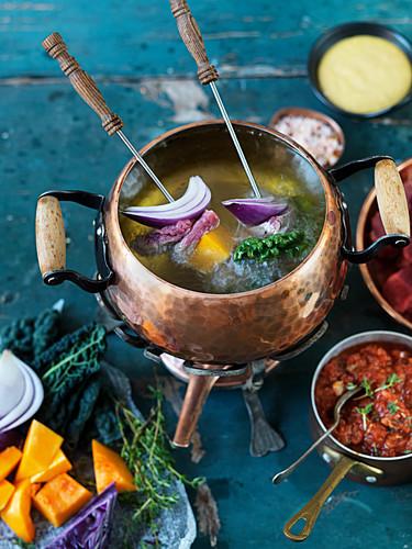 Fondue mit Rindfleisch, Kürbis, Grünkohl, roten Zwiebeln und Salsa