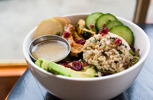 Vegetarische Reisschale mit Eichelkürbis, Kartoffeln, Avocado und Cranberries