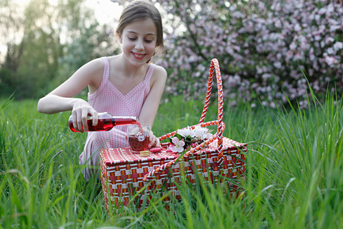 A girl pouring juice into glasses at a picnic in a meadow amongst apple trees
