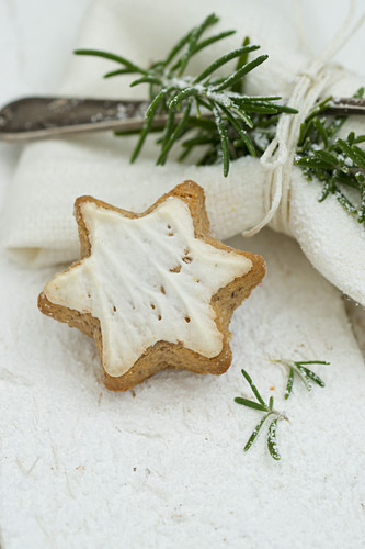 A cinnamon star next to a napkin with a silver fork and a sprig of rosemary