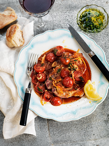 Pork chop with roasted cherry tomatoes and lemon