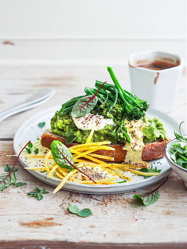 Toast with avocado cream, broccolini, cream cheese, hollandaise sauce and yellow carrot strips