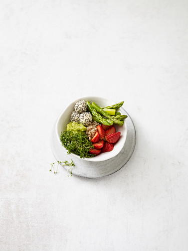 Spring bowl with cheese balls, strawberries and green asparagus