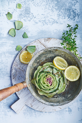 Still life of artichokes with lemon and thyme