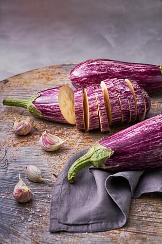 Raw tiger eggplant on tray with garlic