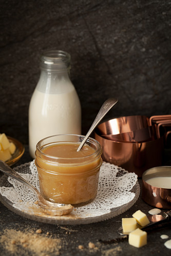 Homemade butterscotch sauce surrounded by its ingredients